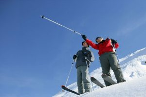 Skier guiding another - featured image for OnTheSnow How To category